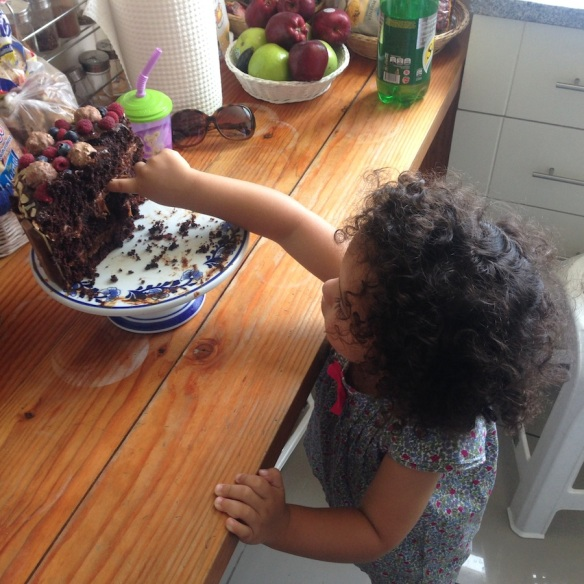 Valentina metiendo dedo a la torta de chocolate